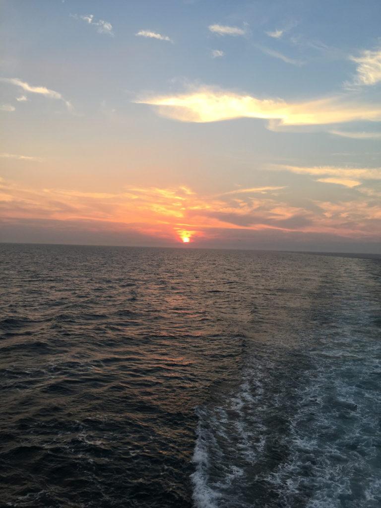 フェリーから見た水平線に沈む夕日