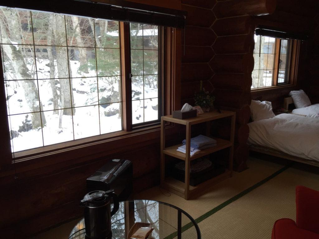 八丁の湯のログハウスの窓から外の眺めを楽しむ